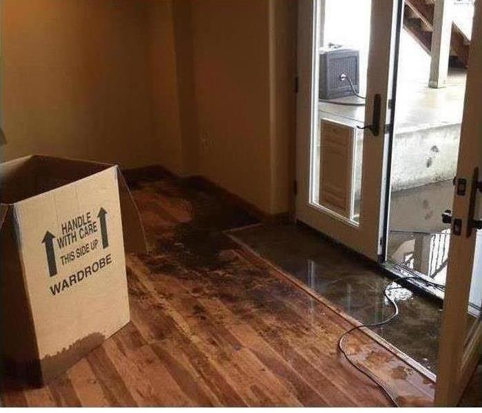 A box sitting in a room on the hardwood floors after it had to be cleared because of a flood